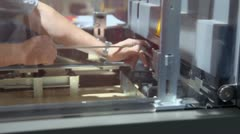 Man screws nut in mechanism of printing machine in conveyer Stock Footage