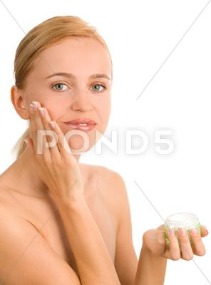 Stock photo of beautiful woman puts a cream 2