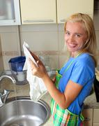 Beautiful woman washes ware Stock Photos