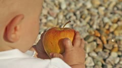 Baby from behind playing with apple Stock Footage