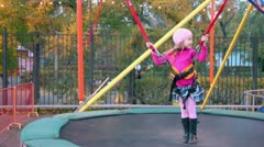 Little girl stands on trampoline with rope support Stock Footage