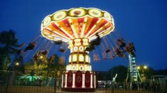 People fly on chairs during ride on round spins carousel Stock Footage