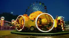 People ride on rotary attraction Kolobok and Ferris wheel Stock Footage