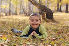 Happy boy in autumn park Stock Photos