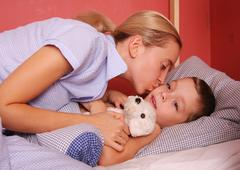 mum puts to bed a sonny 2 - stock photo