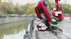 EMERCOM serviceman hooks crashed car which hangs on crane Stock Footage