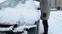 Woman cleaning removing snow car front window brush tool winter Stock Footage