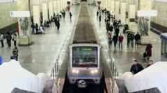 People walk by platforms on both sides of train which rides away Stock Footage
