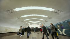 People walk by platform and train rides away from metro station Stock Footage
