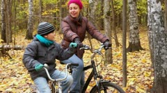 Son speaks with mother when they sit on bikes and look upward Stock Footage