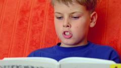 Young boy in blue shirt reads book aloud against red wall Stock Footage