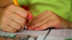 Little girl write slashes by pen on paper, closeup Stock Footage