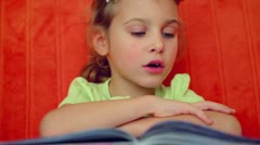 Young girl reads syllables from book aloud against red wall Stock Footage