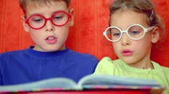 Two kids boy and little girl sit together and read book Stock Footage