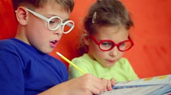 Children sit together, boy writes by pencil and girl watch Stock Footage
