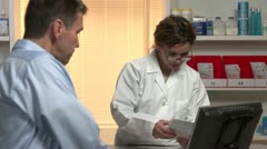 Female pharmacist explaining to male patient about the prescription drug Stock Footage