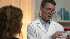 Male pharmacist explaining to patient about the prescription drug Stock Footage