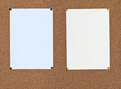 Blue and yellow sheets of paper on cork Stock Photos