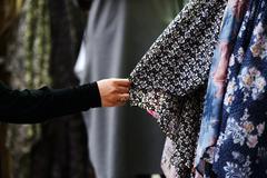 woman choosing clothes at market - stock photo