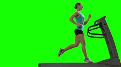 Young woman running on the treadmill in front of green screen, profile Stock Footage