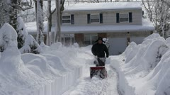 Man uses snow blower to remove snow - 1 Stock Footage