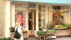 People pass by small flower shop in Vienna Stock Footage