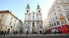 Several people pass by church of Mariahilf at sunny day Stock Footage