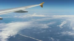 Plane wing in air with clouds and seashore Stock Footage