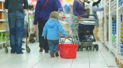 Baby slide shopping basket on floor in supermarket - stock footage