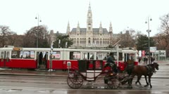 Vehicle with horses passes by the tram against City Hall Stock Footage