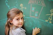 Stock Photo of cute little girl drawing on blackboard