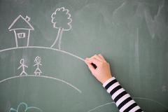 Childs hand drawing on a blackboard Stock Photos