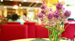 Artificial purple lilies in vase on table in restaurant Stock Footage