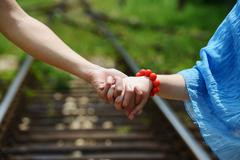 man and woman holding hands - stock photo