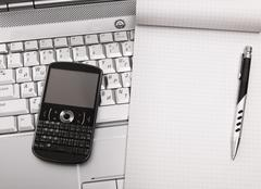 Laptop with hi-tech mobile phone and notepad. Stock Photos