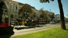 Dolly shot of carriage and tram through the trees on the Vienna boulevard Stock Footage
