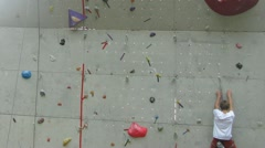 Rock climbing wall on zoom with a young man climbing on contest Stock Footage