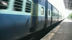 Express passenger train passes through station in India Stock Footage