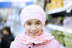 beautiful smiling girl with cap on her head in shopping mall - stock photo