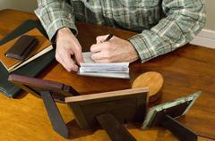 Man writing personal check Stock Photos