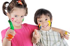 smiling brother and sister with pant on hands and face - stock photo