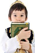 Muslim kid with holy quran Stock Photos