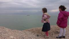 Little girls throw stones to sea Stock Footage