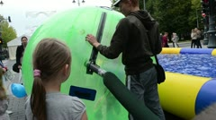 Girl in zorb bubble ball and man inflate air near playground Stock Footage