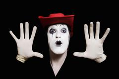 face and hands of mime with dark make-up in red hat - stock photo