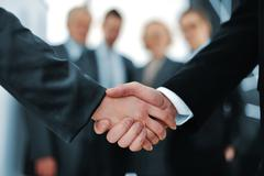 Handshake in front of business people Stock Photos