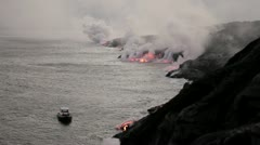 Tour boat close to molten lava entering ocean Stock Footage