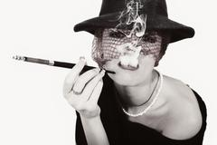Woman with cigarette in mouthpiece in hat with vei Stock Photos