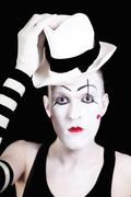 Mime with red bow ina white hat and striped gloves Stock Photos