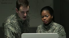 Female soldier showing fellow soldier on laptop Stock Footage